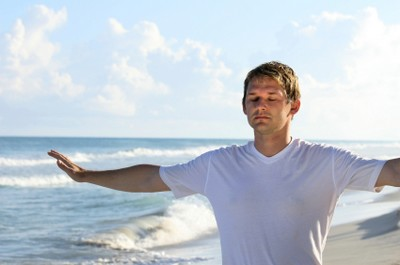 man doing stretching exercises on the beach